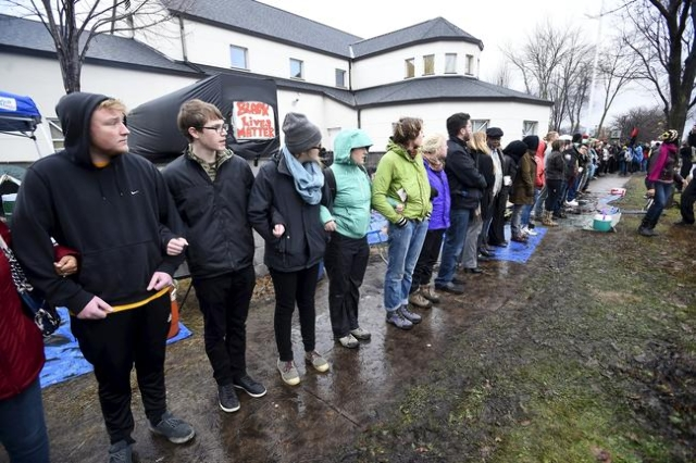 Protesters form a human chain in front of a north Minneapolis police precinct and around their encampment during a protest in response of Sunday's shooting death of Jamar Clark by police off ...