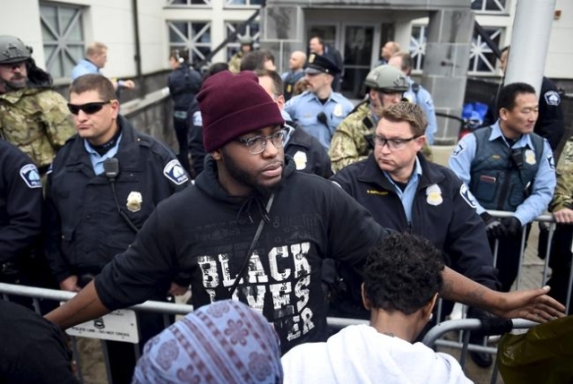 A member of Black Lives Matter tries to keep protesters back from the police line in front of a north Minneapolis police precinct during a protest in response of Sunday's shooting death of J ...