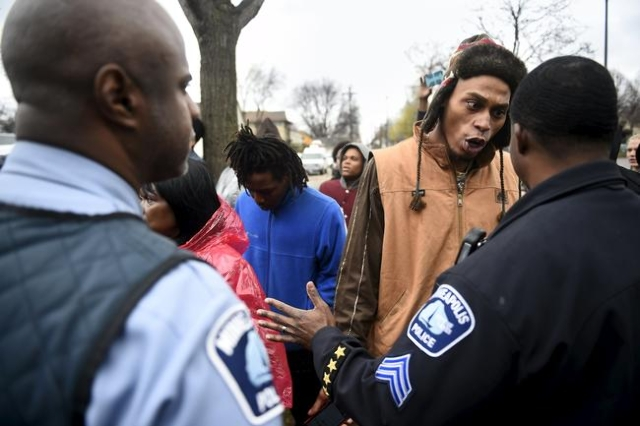 A protester argues with a police officer in front of a north Minneapolis police precinct during a protest in response of Sunday's shooting death of Jamar Clark by police officers in Minneapo ...