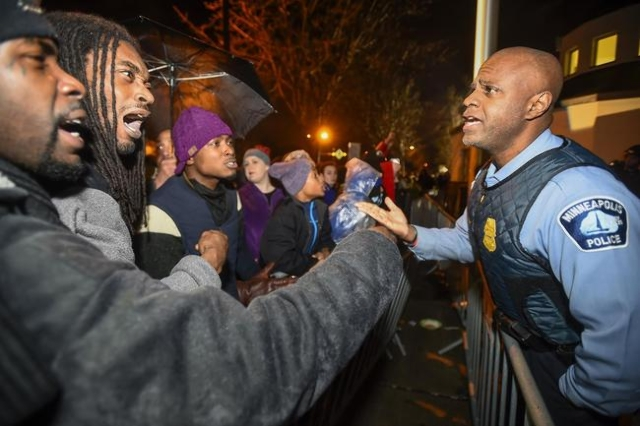 A police officer talks with demonstrators in front of a north Minneapolis police precinct during a protest in response of Sunday's shooting death of Jamar Clark by police officers in Minneap ...