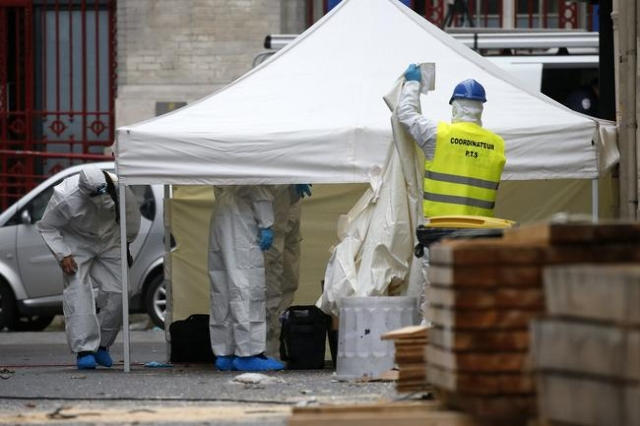 Forensics of the French police work outside a building in Saint-Denis, near Paris, Nov. 19, 2015, the day after a police raid to catch fugitives from Friday night's deadly attacks in the Fre ...