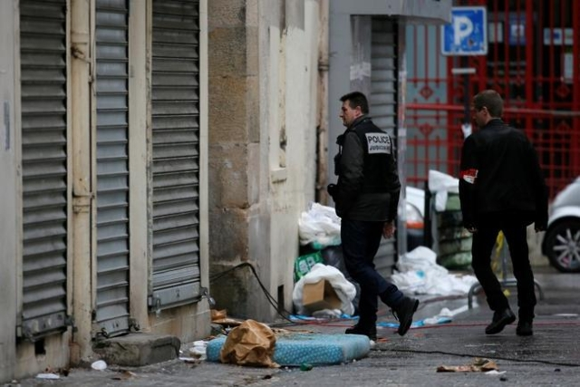A member of French judicial police and a French plainclothes policeman walk outside a building in Saint-Denis, near Paris, Nov. 19, 2015, the day after a police raid to catch fugitives from Friday ...