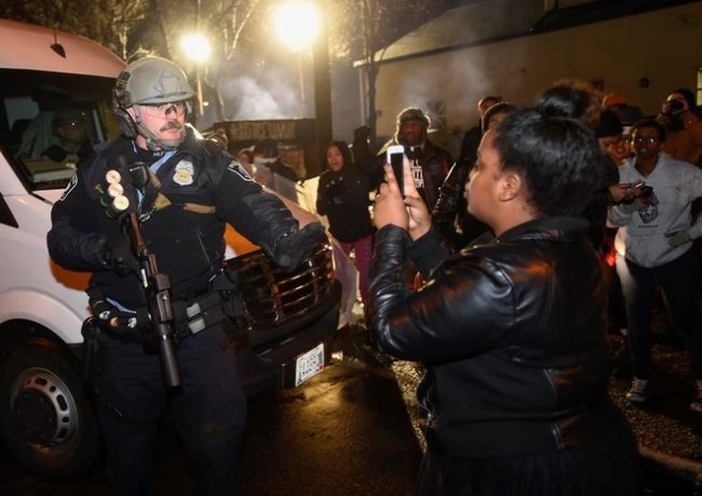 A police officer tells a women to back up as she photographs him in front of a north Minneapolis police precinct during a protest in response of Sunday's shooting death of Jamar Clark by pol ...