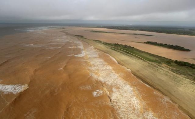 A general view the sea (L) and Rio Doce (Sweet River), which was flooded with mud after a dam owned by Vale SA and BHP Billiton Ltd burst, on the coast of Espirito Santo in Povoacao Village, Brazi ...
