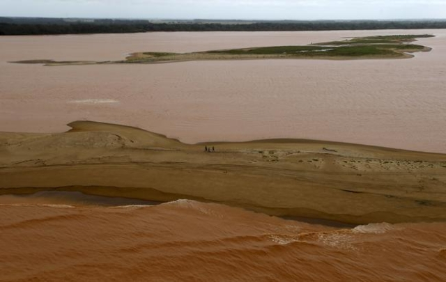 People walk between the sea (bottom) and the Rio Doce (Doce River), which was flooded with mud after a dam owned by Vale SA and BHP Billiton Ltd burst, as the river joins the sea on the coast of E ...
