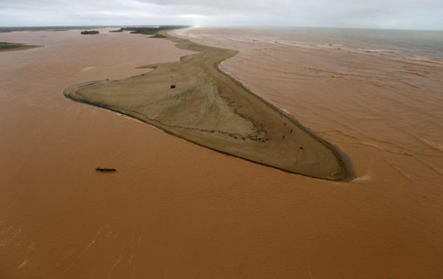 A boat is seen on the mouth of Rio Doce (Sweet River), which was flooded with mud after a dam owned by Vale SA and BHP Billiton Ltd burst, as the river joins the sea on the coast of Espirito Santo ...