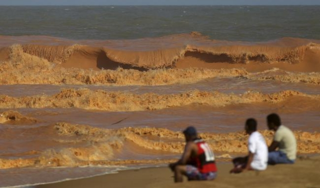 Men look on from the banks of Rio Doce (Sweet River), which was flooded with mud after a dam owned by Vale SA and BHP Billiton Ltd burst, as the river joins the sea on the coast of Espirito Santo  ...