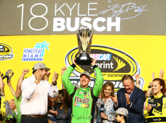 Nov 22, 2015; Homestead, FL, USA; NASCAR Sprint Cup Series driver Kyle Busch hoists the Sprint Cup championship trophy in victory lane after winning the Ford EcoBoost 400 to win the Sprint Cup cha ...