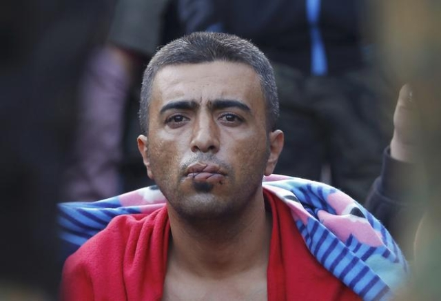 A migrant with his mouth sewn shut in protest sits at the border with Greece near the village of Gevgelija, Macedonia November 23, 2015. (Ognen Teofilovski/Reuters)
