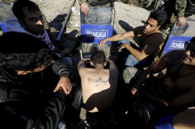Stranded Iranian migrants sit on rail tracks at the border between Greece and Macedonia in front of Macedonian riot police near the Greek village of Idomeni November 23, 2015. (Yannis Behrakis/Reu ...