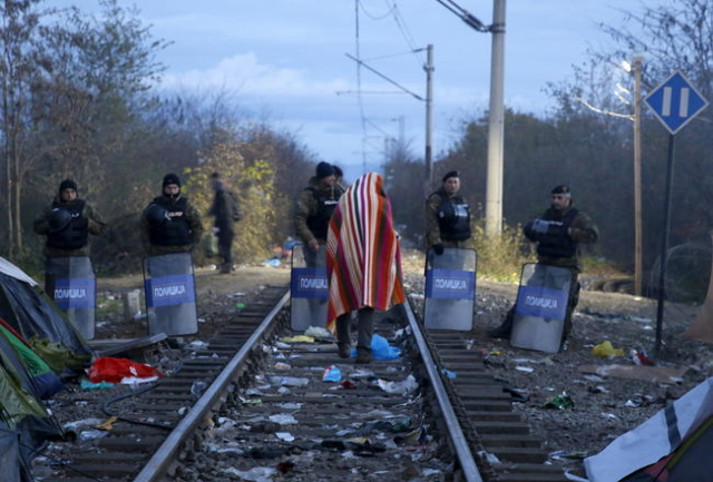 Stranded Iranian migrant Hamid, 34, an electrical engineer from the Iranian town of Sanandij walks on rail tracks in front of Macedonian riot police guarding the border between Greece and Macedoni ...