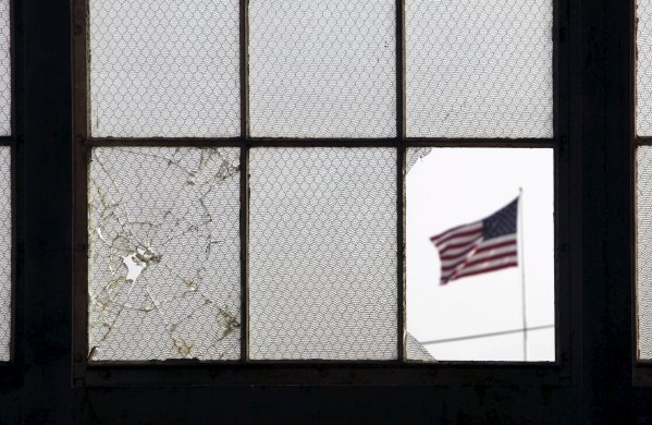 In this 2009 file photo, reviewed by the U.S. military, an American flag fluttering in the wind is pictured through a broken window from inside an airplane hangar used for media activities at Camp ...