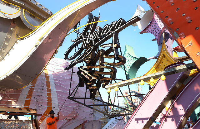 Larry Hernandez, left, of Jones Sign, holds the rope as he lowers a newly restored sign from Liberace Museum at The Neon Museum where it joined their existing Boneyard collection, on Friday, Sept. ...