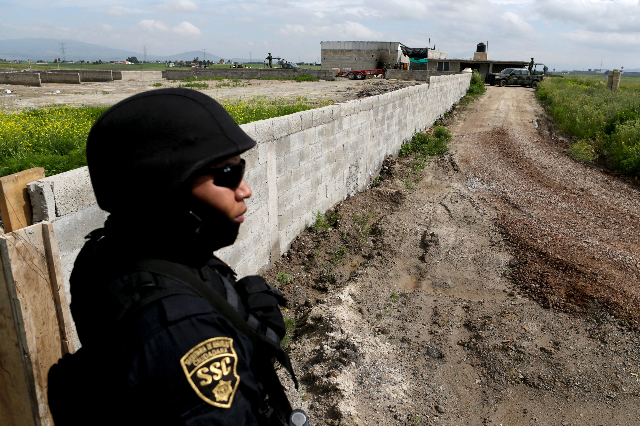 A policeman keeps watch outside the site where a tunnel, connected to the Altiplano Federal Penitentiary and used by drug lord Joaquin 'El Chapo' Guzman to escape, was located in Almol ...