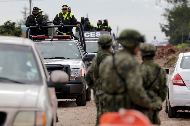Policemen patrol as soldiers stand at a checkpoint outside the Altiplano Federal Penitentiary, after drug lord Joaquin 'El Chapo' Guzman escaped, in Almoloya de Juarez, on the outskirt ...