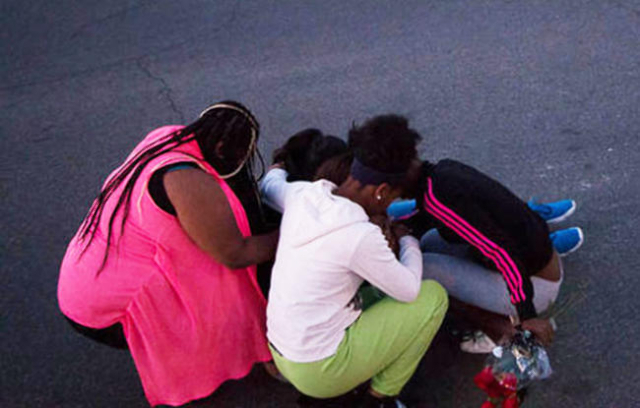 Mourners gather Saturday, Nov. 21, 2015, near the intersection of Goldfield Street and Honey Locust Drive, a day after a shooting in front of Mojave High School that left a 16-year-old boy dead. ( ...