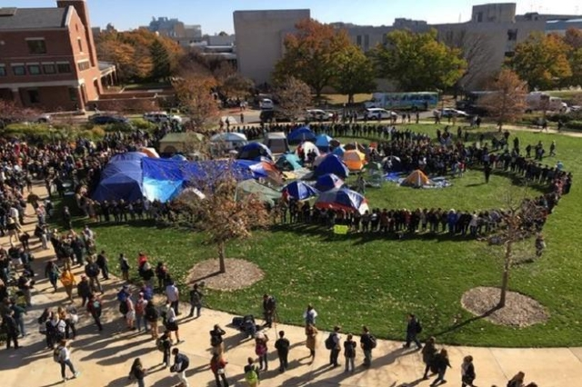 Students and faculty members form a circle around a campsite occupied by protesters at the University of Missouri. )Lindsay Gloor/Twitter/CNN)