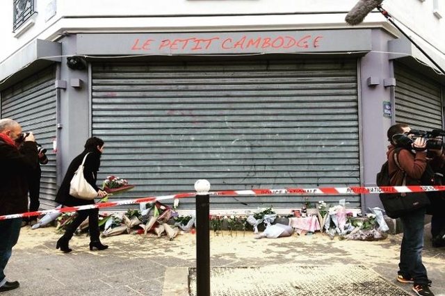 A woman lays flowers at the scene of the Paris shooting of Le Petit Cambodge restaurant. Parisians wandering around in shock, looking at the bullet holes in the windows. (Atika Shubert/CNN)