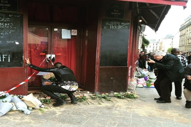 Man lays flowers at Le Carillon. (Atika Shubert/CNN)