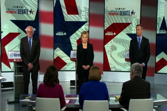 The Democratic presidential candidates hold a moment of silence for the victims of the Paris terror attacks before their debate in Des Moines. (CBS/CNN)