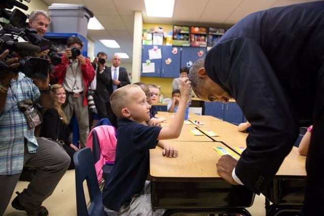 President Barack Obama allows first-grader Edwin Caleb touch his hair during a classroom visit at Clarence Tinker Elementary School at MacDill Air Force Base in Tampa, Florida, Sept. 17, 2014. (La ...