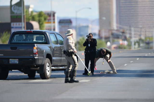 Las Vegas Police officers investigate a crash in which a car hit a pedestrian at the intersection of Spring Mountain Road and Lindell Road of on Thursday, Oct. 22, 2015, in Las Vegas. (Brett LeBla ...