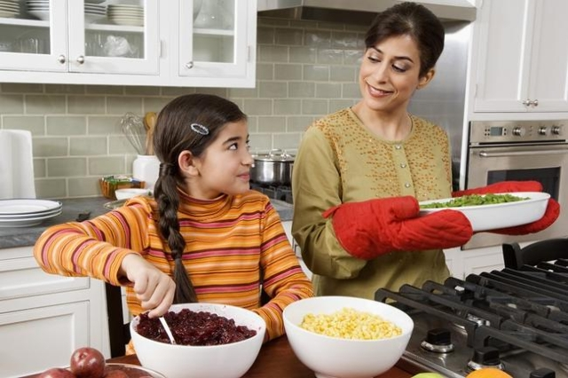 Mother and daughter cooking Thanksgiving meal in kitchen (Thinkstock)
