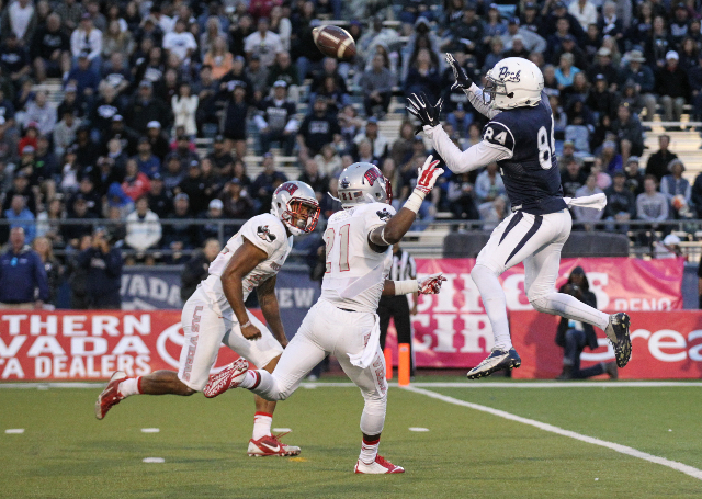 UNR's Jerico Richardson 84) jumps to catch the ball for a touchdown as UNLV's Peni Vea, left, and Darius Mouton attempt to block during their football game at Mackay Stadium in Reno, N ...