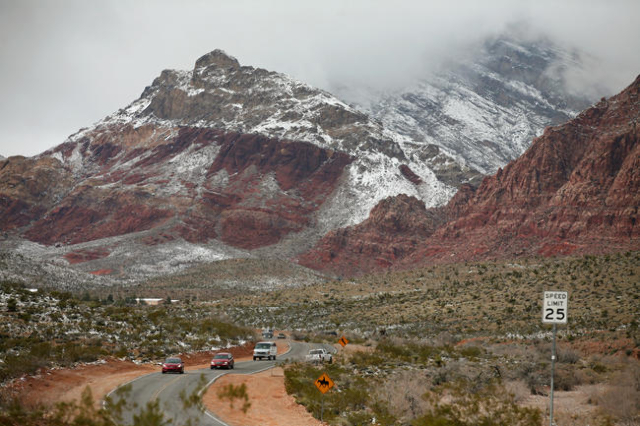 Cars travel along Calico Basin Road and snowfall can be seen at Red Rock Canyon National Conservation Area Monday, Feb. 23, 2015, in Las Vegas. (Ronda Churchill/Las Vegas Review-Journal)