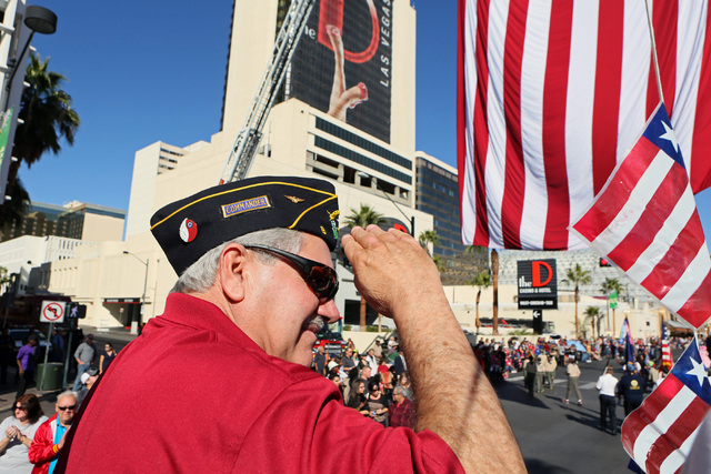 Rod Carlone, U.S. Navy veteran and commander of Las Vegas American Legion Post 8, salutes a crowd of parade watchers while riding in the American Legion Post 8 float in the Veterans Day parade Mon ...