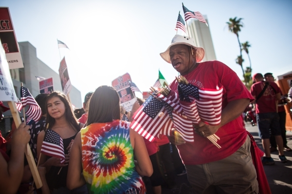 Olee Stewart, right, hands out flags as Culinary Union Local 226 members and supporters prepare to protest against the Trump International Hotel along Fashion Show Drive in Las Vegas on Friday, Au ...