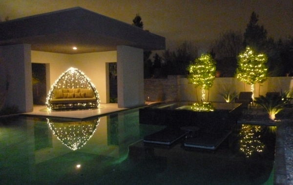 The pool area is a perfect place to string lights, which reflect off the water.  COURTESY COURTNEY LIGHTS