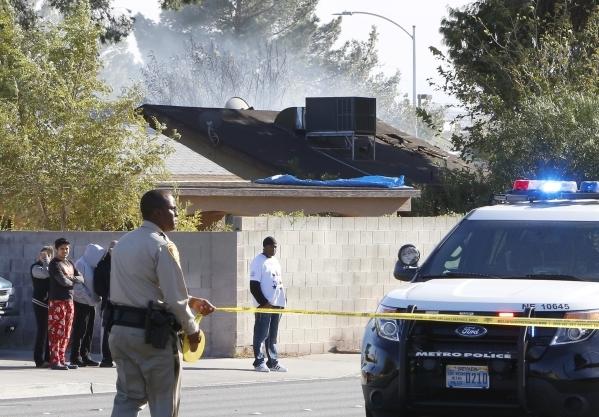 Smoke is seen from a burning house as a Metro police officer blocks off Lamb Boulevard near Sherrill Avenue, Monday, Nov. 16, 2015. Bizuayehu Tesfaye/Las Vegas Review-Journal Follow @bizutesfaye