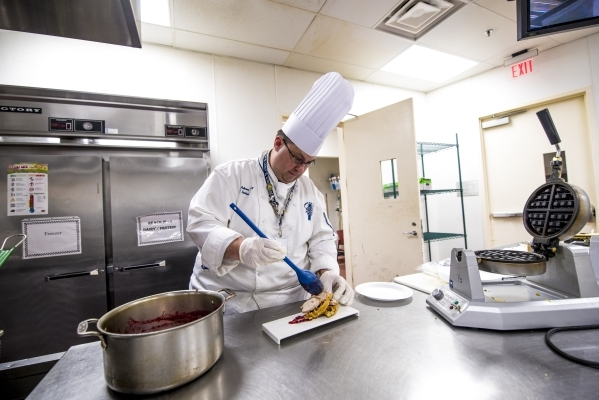 Chef Michael Anderson plates a dish of waffles made from traditional Thanksgiving stuffing, turkey, and topped with cranberry sauce, during a cooking demonstration at Le Cordon Bleu College of Cul ...