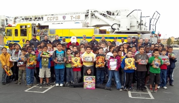Children and firefighters pose in this undated photo during the Fill the Fire Truck drive. The annual holiday toy drive co-hosted by Firefighters of Southern Nevada Burn Foundation is planned thro ...