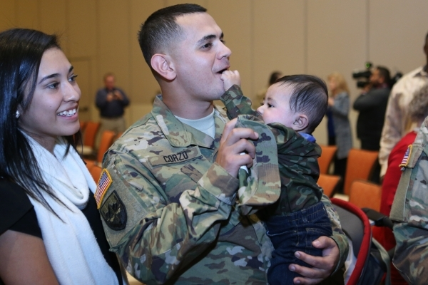 Sgt. Miguel Corzo holds his 5-month-old son Ethan as his wife Karla look on during his mobilization ceremony with about 35 other soldiers of the Nevada Army National Guard´s 137th Military Poli ...