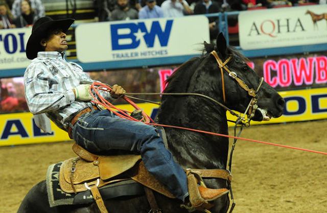 Team roper Junior Nogueira from Scottsdale, Ariz., pulls a rope tight on a calf a calf during the first go-round of the 2015 Wrangler National Finals Rodeo at the Thomas & Mack Center in Las V ...