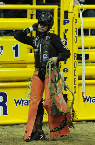 Bull rider Sage Kimzey from Strong City, Okla., reacts after being bucked from his bull during the first go-round of the 2015 Wrangler National Finals Rodeo at the Thomas & Mack Center in Las  ...