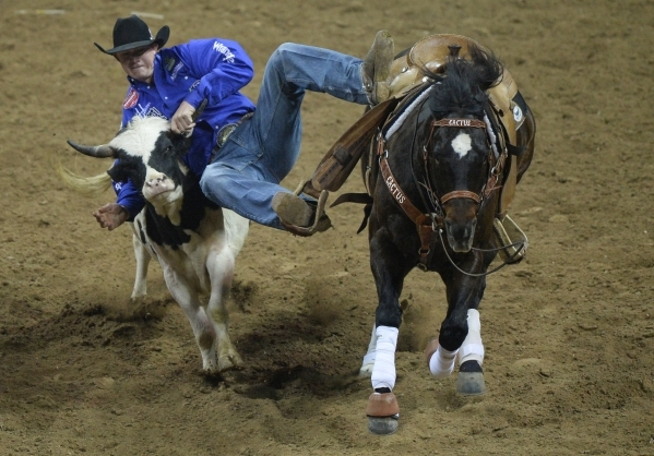 Ty Erickson, of Helena, Mont., takes down a steer in the streer wrestling competition on the second day of the 2015 Wrangler National Finals Rodeo at the Thomas & Mack Center in Las Vegas on F ...
