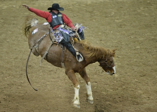 Rusty Wright, of Milford, Utah, rides Major Huckleberry in the Saddle Bronc Riding competition on the second day of the 2015 Wrangler National Finals Rodeo at the Thomas & Mack Center in Las V ...