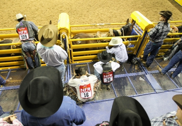 Isaac Diaz (16), of Desdemona, Texas, crouches down and takes a moment to himself before competing in the Saddle Bronc Riding competition on the second day of the 2015 Wrangler National Finals Rod ...