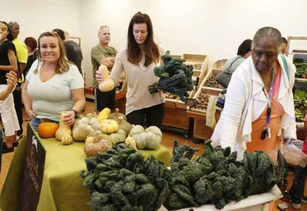 Dalia Sager, center, holds winter squash and kale while shopping at the Downtown Summerlin Farmers Market March 14. Bizuayehu Tesfaye/View file photo)