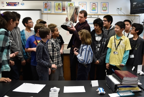 NASCAR Sprint Cup Series champion Kyle Busch, center, moves his championship trophy before taking a group photo during a visit to a STEM class at Lawrence Junior High School on Tuesday, Dec. 1, 20 ...