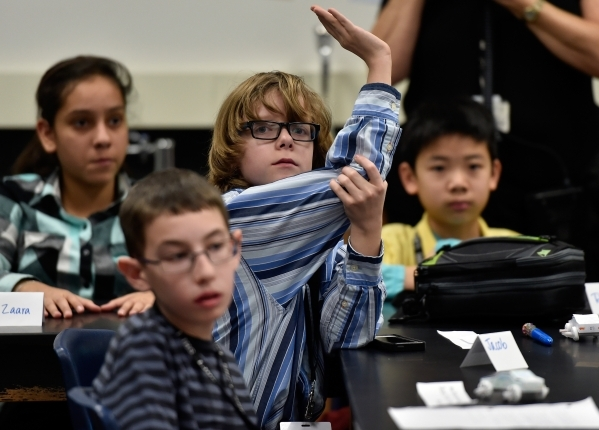 Student Jacob Zabel, center, raises his hand to ask a question to NASCAR Sprint Cup Series champion Kyle Busch during his class at Lawrence Junior High School on Tuesday, Dec. 1, 2015, in Las Vega ...