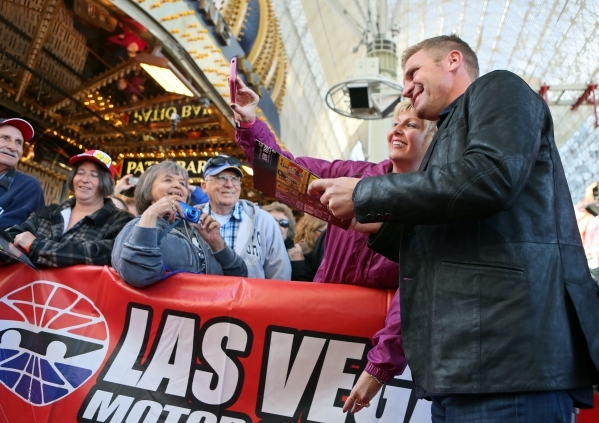NASCAR driver Clint Bowyer, right, takes a photo with fan Rachel Klosterman, of Wyndmer, N.D., during a NASCAR FanFest event at Fremont Street Experience Wednesday, Dec. 2, 2015, in Las Vegas. Dri ...