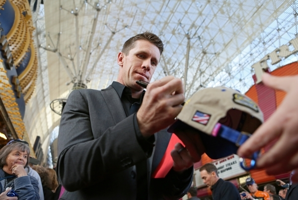 NASCAR driver Carl Edwards autographs a hat for a fan during a NASCAR FanFest event at Fremont Street Experience Wednesday, Dec. 2, 2015, in Las Vegas. Drivers met fans while walking a red carpet  ...