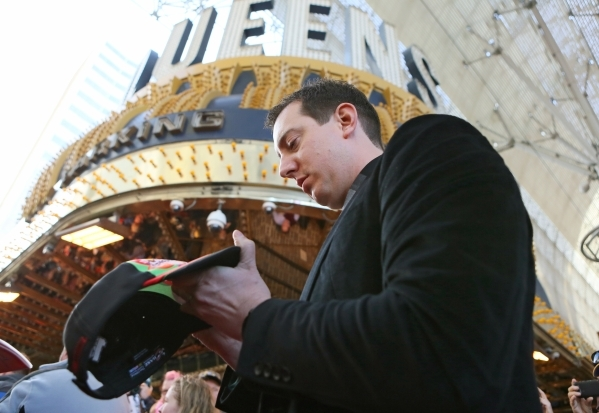 NASCAR driver Kyle Busch autographs a hat for a fan during a NASCAR FanFest event at Fremont Street Experience Wednesday, Dec. 2, 2015, in Las Vegas. Drivers met fans while walking a red carpet an ...