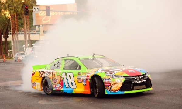 2015 NASCAR Sprint Cup champion and native Las Vegan Kyle Busch performs a burnout at the intersection of Spring Mountain and Las Vegas Boulevard during the NASCAR Victory Lap celebration a part o ...