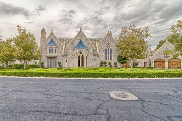 The home at 2928 Coast Line Court in the Lakes is festooned with towering triangular exterior cast stone walls embedded with beveled and stained-glass windows, a massive 700-pound mahogany carved  ...