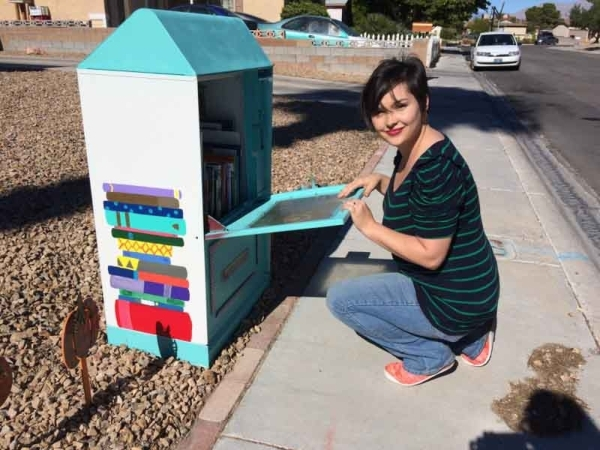 Katie Krikorian reaches into a Little Free Library at 4004 Dale Evans Drive near Rainbow Boulevard and Alexander Road Oct. 30. Her LFL is a repurposed newspaper dispenser. Jan Hogan/View